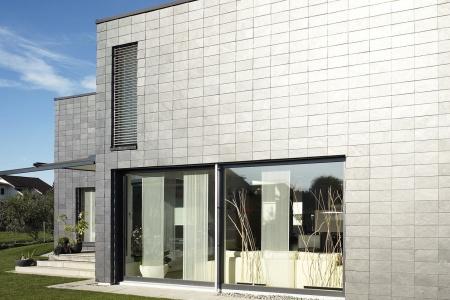 Graue Fassade mit grossen Wohnfenstern